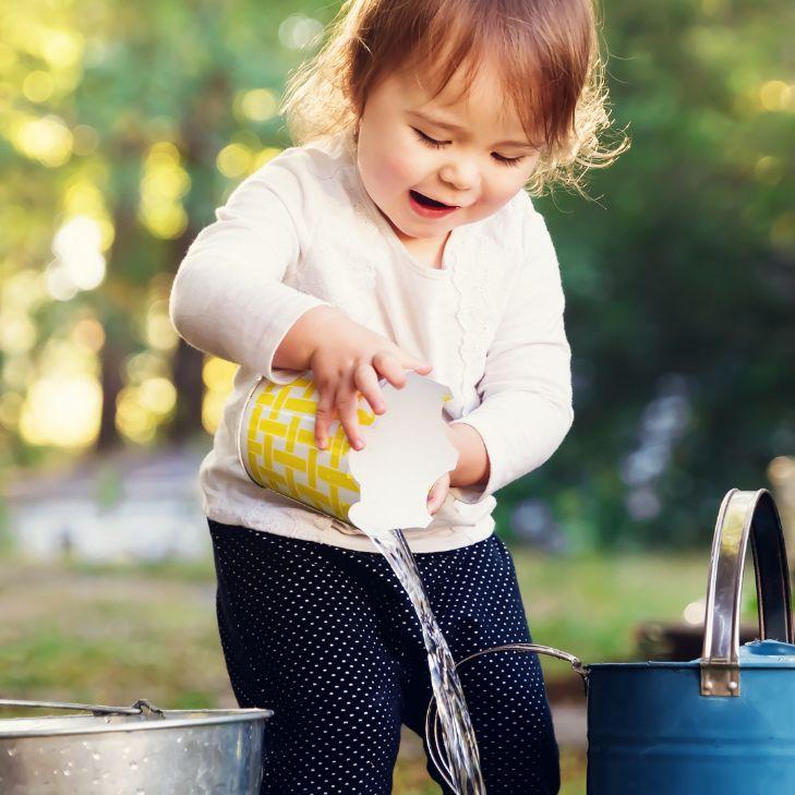 çocuk bahçede suyla oynuyor